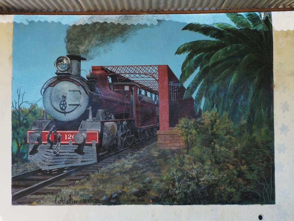 An old steam train comes across the old steel bridge of 25 de Agosto