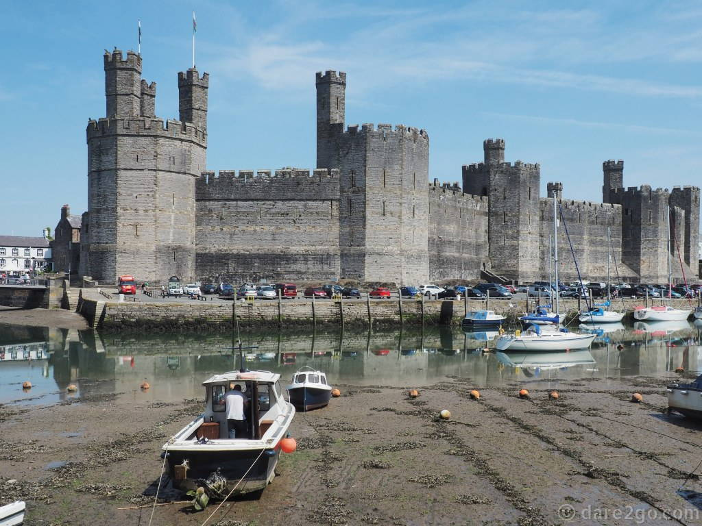 World Heritage Listed castles in Wales: when the tide is high you get lovely reflections on the water of the castle in Caernarfon. Note the horizontal bands of different stone colours on the outer castle wall.